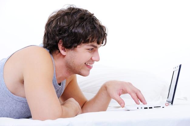Профиль портрет веселого молодого мужчины, печатающего на ноутбуке, лежа в своей постели
