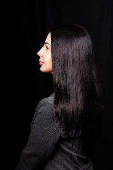 Профиль портрет милой великолепной девушки с сияющей улыбкой пухлыми губами в повседневном платье на черном фоне с копией пространства пустого пространства.