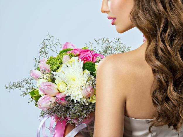 手に花を持つ女の子のプロフィールの肖像画。ハーフフェイス
