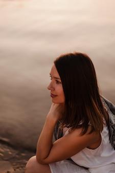 Профиль портрет красивой молодой женщины в сумерках заката с морской гладью на заднем плане