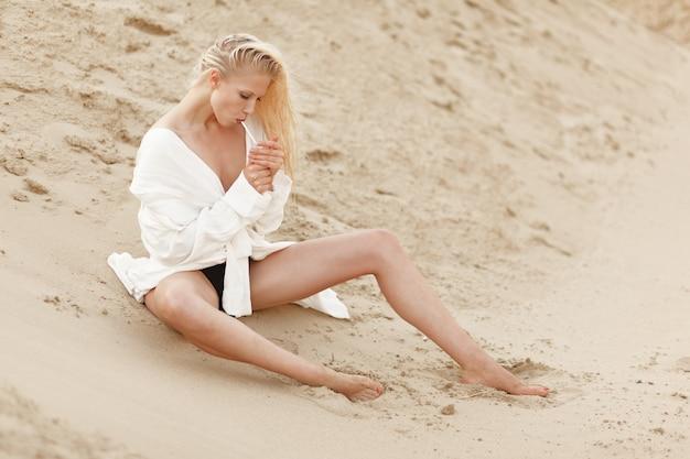 Профиль портрет сексуальная молодая блондинка женщина в белой большой рубашке, курить, сидя на песчаном грунте. портрет красоты.
