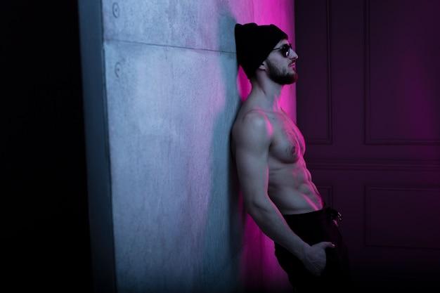 暗いスタジオでポーズをとって帽子をかぶった上半身裸のフィットの残忍な若い男のプロフィールの肖像画