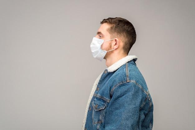 光の表面に対して横を向いている保護医療マスクの若い男のプロフィールの肖像画。
