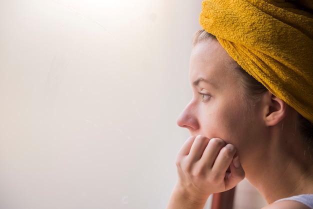 혼자 창 밖을보고 앉아 젊은 여자의 프로필 초상화. 뭔가 대해 생각하는 창 근처 슬픈 소녀입니다.