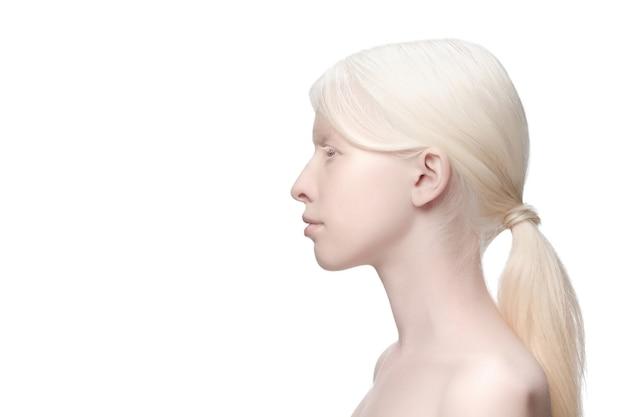 プロフィール。白いスタジオの背景に分離された美しいアルビノの女性の肖像画。美容、ファッション、スキンケア、化粧品のコンセプト。コピースペース。手入れの行き届いた肌、みずみずしい表情。包含と多様性。