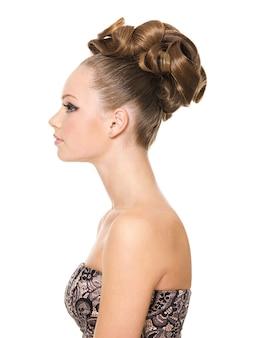 創造的な巻き毛の髪型を持つ美しいティーンエイジャーの女の子のプロフィールの肖像画-