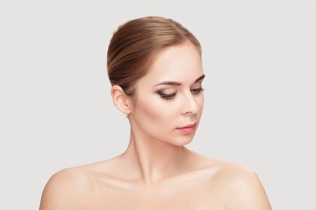 Профиль портрет красивой молодой блондинки с зелеными глазами на сером фоне крупным планом. девушка с чистой кожей
