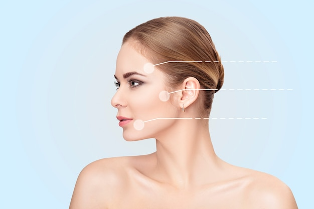 회색 배경 근접 촬영에 녹색 눈을 가진 아름 다운 젊은 금발 여자의 프로필 초상화. 깨끗한 피부를 가진 소녀