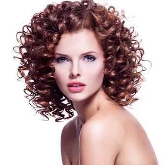 ブルネットの巻き毛を持つ美しい若いセクシーな女性のプロフィールの肖像画-白で隔離。
