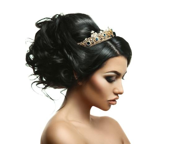 白い背景で隔離のスタジオで創造的な髪型と頭の上の王冠を持つ美しさの若いブルネットのプロフィールの肖像画