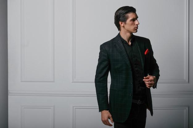 Профиль портрет уверенно молодого человека в черном костюме с красным шелковым шарфом в кармане, на белом фоне. горизонтальный вид.