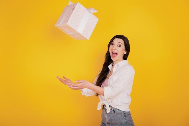 Профиль портрет возбужденной фанки красивой девушки бросает подарочную коробку с открытым ртом на желтом фоне