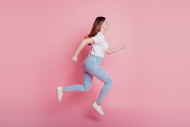 Портрет профиля игривой сумасшедшей девушки, прыгающей в воздухе, одетой в повседневный джинсовый наряд на розовой стене