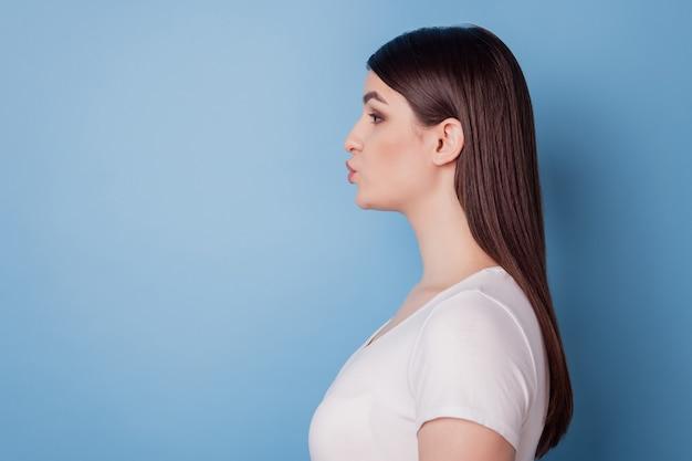 ロマンチックなかわいい女性のプロフィールの肖像画は、空のスペースを見て青い背景に空気のキスを送信します
