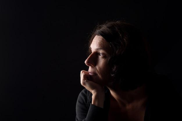あごに手と黒の背景で考えている深刻な女性のプロフィールの肖像画