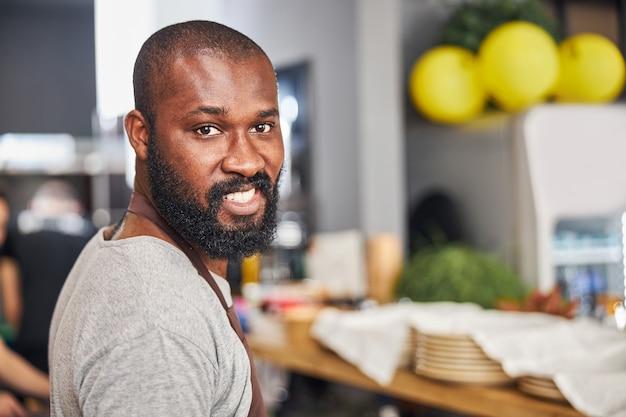 カフェで料理をしながら楽しい時間をエプロンで笑顔のひげを生やしたアフリカ系アメリカ人シェフのプロフィールの肖像画