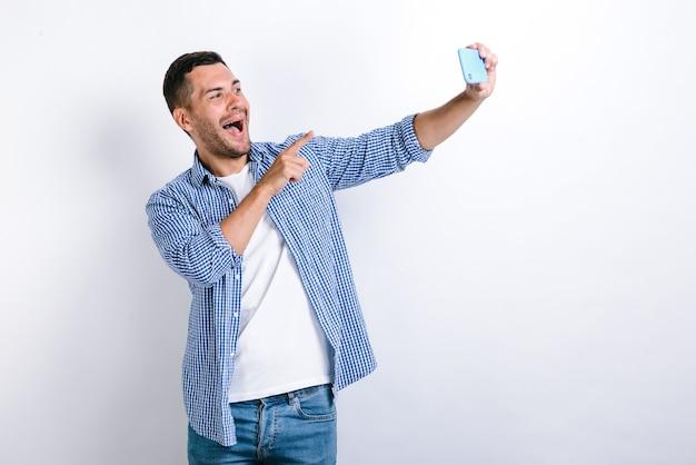 셀카를 찍거나 화상 통화를 하고 몸짓으로 말하는 수염을 가진 젊은 성인 남자의 프로필 초상화. 온라인 커뮤니케이션 개념입니다. 흰색 배경에 고립 된 실내 스튜디오 셔츠