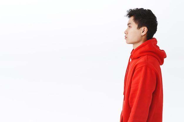 빨간 후드티를 입은 젊은 아시아 남성의 프로필 초상화는 진지하고 방해받지 않는 표정으로 왼쪽을 바라보며 흰 벽, 라이프스타일, 사람, 감정에 대한 개념입니다.