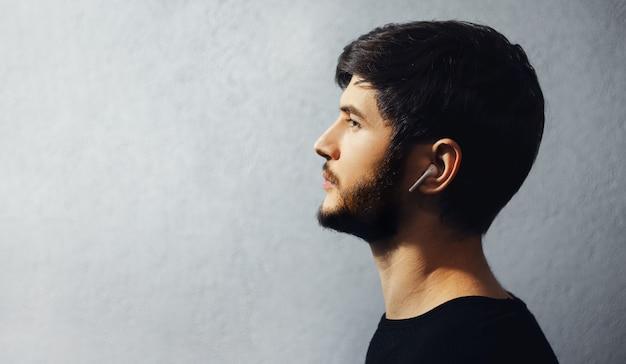 ワイヤレスイヤホンを使用して若い思いやりのある男のプロフィールの肖像画