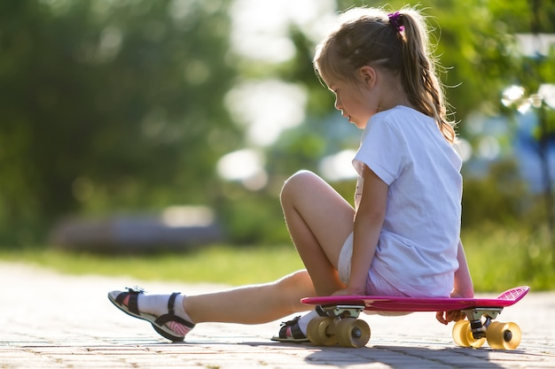 Profile portrait of pretty small long haired blond girl in white clothing sitting on skateboard