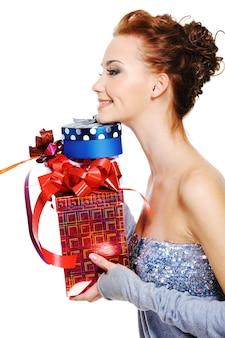Ritratto di profilo di una femmina abbastanza giovane con un mucchio di scatole regalo di natale