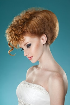 Profile portrait of a red hair  young woman with hairdressed and speckle, with bare shoulders, wearing a wedding dress, over blue wall.