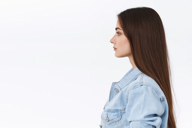 Profile portrait serious-looking, determined and confident attractive modern 20s woman in denim jacket, standing in elevator or subway, waiting in queue with calm unbothered, casual expression