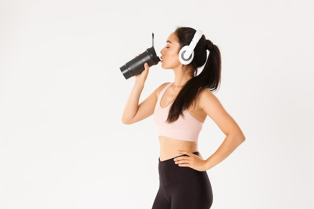 Profile portrait of sexy asian fitness coach, woman in headphones drinking water from bottle during workout in gym, standing white background.
