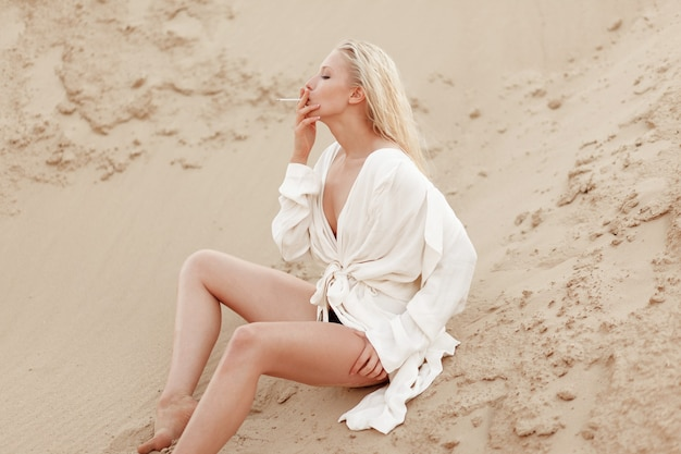 Profile portrait of a sexy young blonde woman in white large shirt, smoking sitting on the sand ground. outdoors portrait.