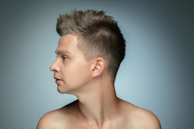Profile portrait of shirtless young man isolated on grey wall