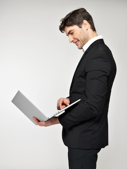 Profile portrait of smiling happy businessman with laptop in black suit.
