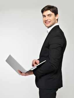 Profile portrait of smiling happy businessman with laptop in black suit.