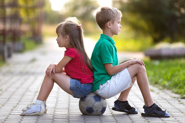 Profile portrait of two cute blond children, smiling boy and long-haired girl sitting on soccer ball.