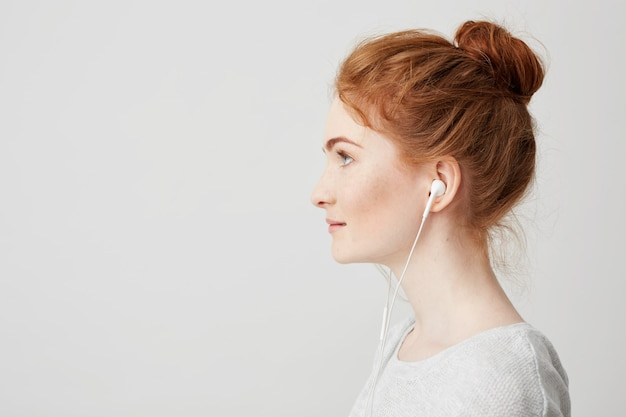 Profile portrait of young beautiful tender redhead girl with bun in headphones smiling .