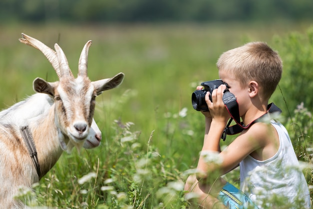 Profile portrait of young blond cute handsome child boy taking picture of funny curious goat.