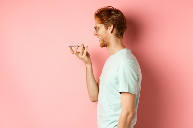 프로필 초상화 빨간 머리를 가진 젊은 남자, 분홍색 배경 위에 서있는 가상 비서에게 말하는 스마트 폰에 음성 메시지를 녹음하는 동안 기쁘게 웃고.