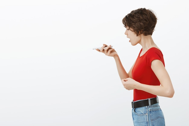 Profile portrait of young stylish woman using phone recorder, voice message at smartphone