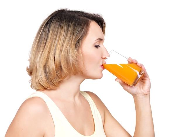 Il ritratto di profilo di una giovane donna beve il succo d'arancia isolato su bianco.