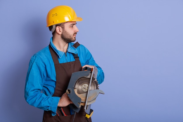 Profile of professional builder holding circular saw in both hands