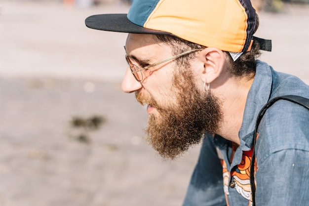 Profile of a redheaded boy with a beard and a cap wearing a printed denim shirt