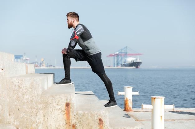 Profile of runner near the sea.