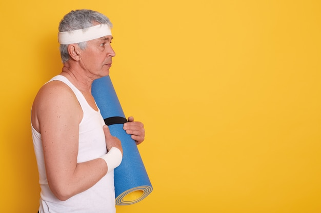 Profile of senior man wearing white t shirt and head band, holding yoga mat in hands, looking straight ahead