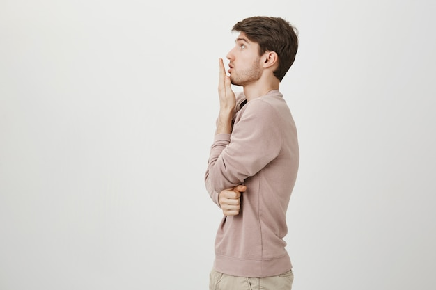 Profile of shocked guy gasping, cover mouth with hand and staring left