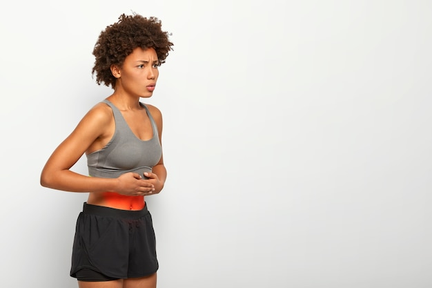 Profile shot of afro american female model suffers from stomachache, has abdominal pain, touches belly, wears top and shorts, frowns face from unpleasant feelings, poses against white background