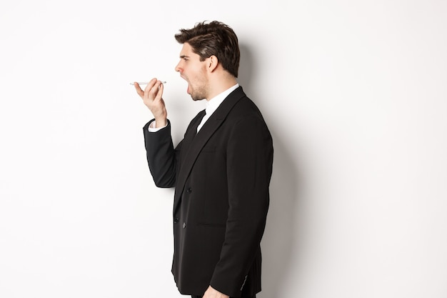 Profile shot of angry businessman in black suit, shouting at speakerphone and looking mad, recording voice message, standing over white background
