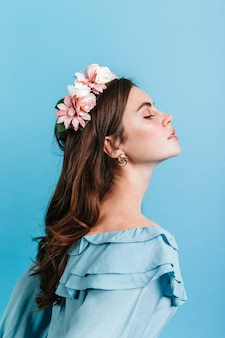 Profile shot of aristocratic girl in blouse with frill. lady with flowers in her hair posing proudly against blue wall.