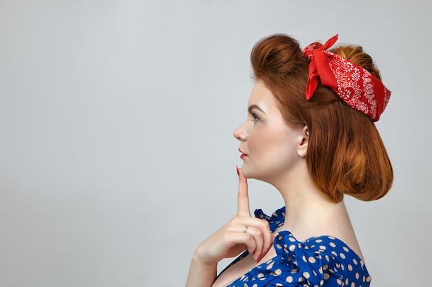 Colpo di profilo di attraente giovane femmina pensierosa in abito blu punteggiato e fascia rossa tenendo il dito sul mento, pensando a qualcosa di importante