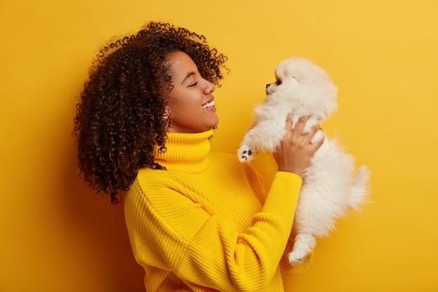 Colpo di profilo della donna riccia bruna posa con spitz bianco, ha umore giocoso, animali domestici piccolo cane soffice, rilassarsi a casa, essere migliori amici, soddisfatti dopo una passeggiata all'aperto.