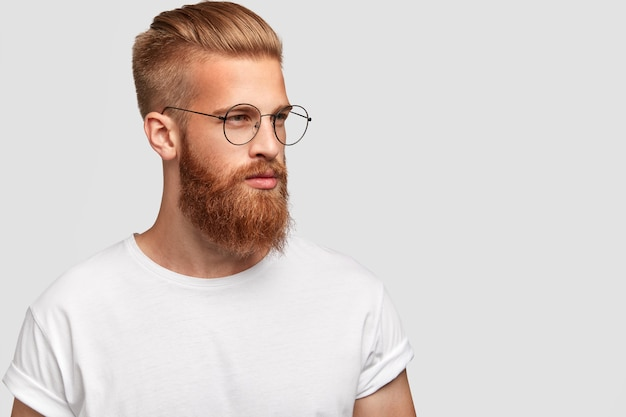 Profile shot of brutal man with thick foxy beard, wears round glasses and looks thoughtfully aside