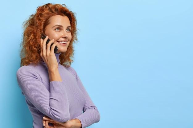 Profile shot of cheerful ginger woman talks in roaming, calls via smartphone